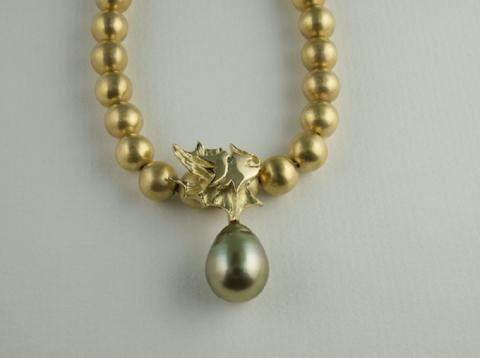 18ct gold beads and carved gold dragon with green Pearl and Sapphire eye