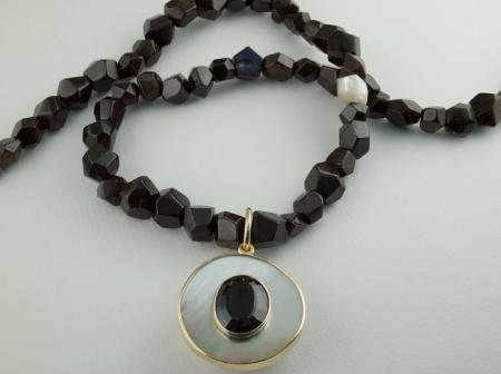 Mother of Pearl holding an oval Garnet on Garnet crystal beads