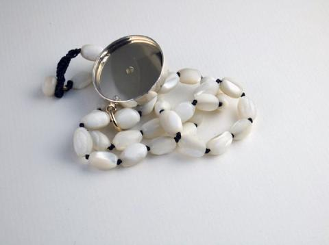 Reverse of necklace with pearl and watch glass