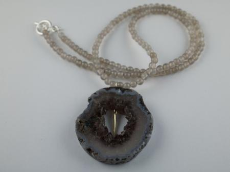 Geode with gold needle sudpended