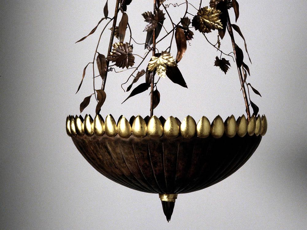 Copper bowl with gum and vine leaves. The uplight scatters leaves on the ceiling.