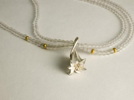 Carved silver Lilly on crystal beads with 22ct details