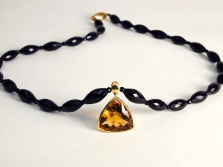 Citrine set in gold on black Spinel beads