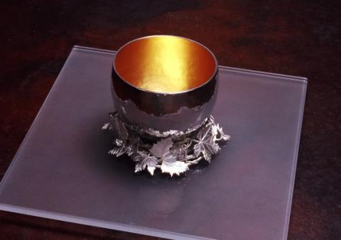 Silver cup /gold plated resting in a wreath of vine leaves on glass plate.